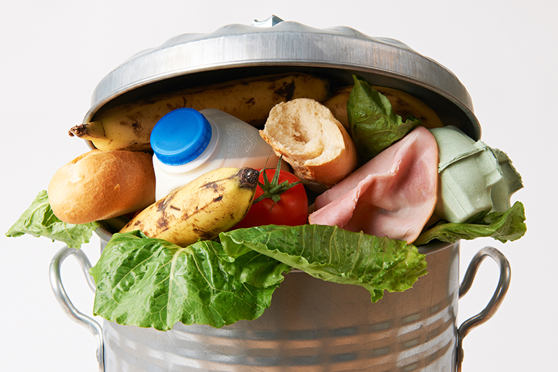 Stock image showing edible food thrown into a trash can.
