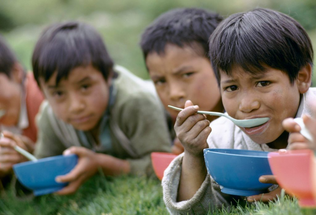 Children lying on the ground eating food from bowls.