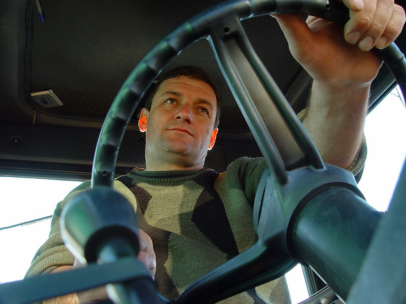 A photo of a man driving a truck.