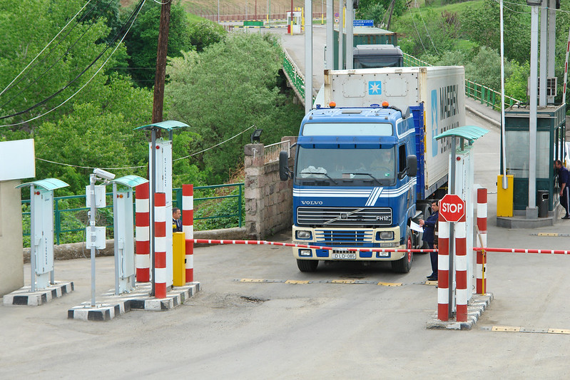A photo of a shipping truck stopped at a gate.