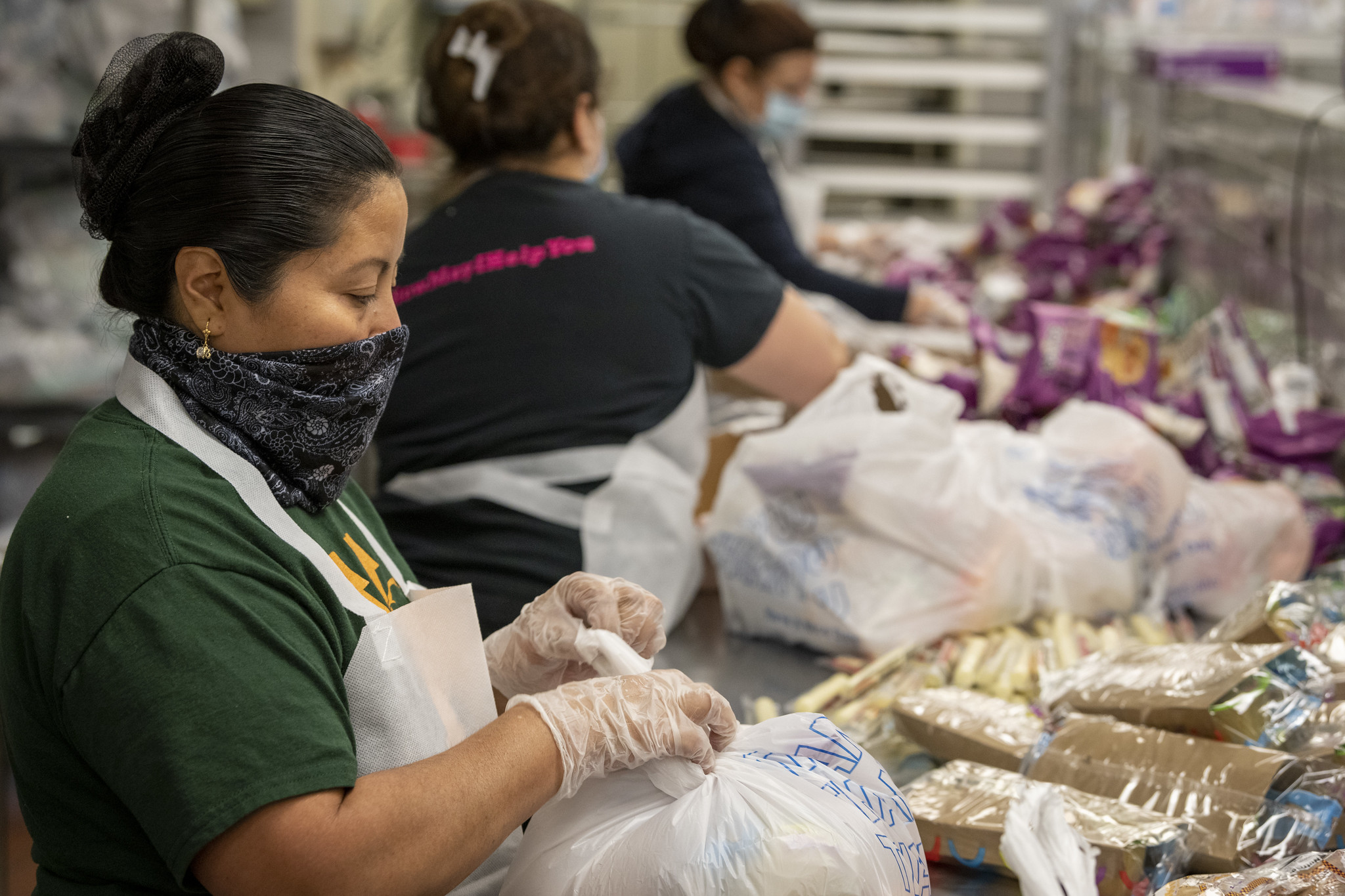 Workers prepare Grab-and-Go Meals in plastic bags.