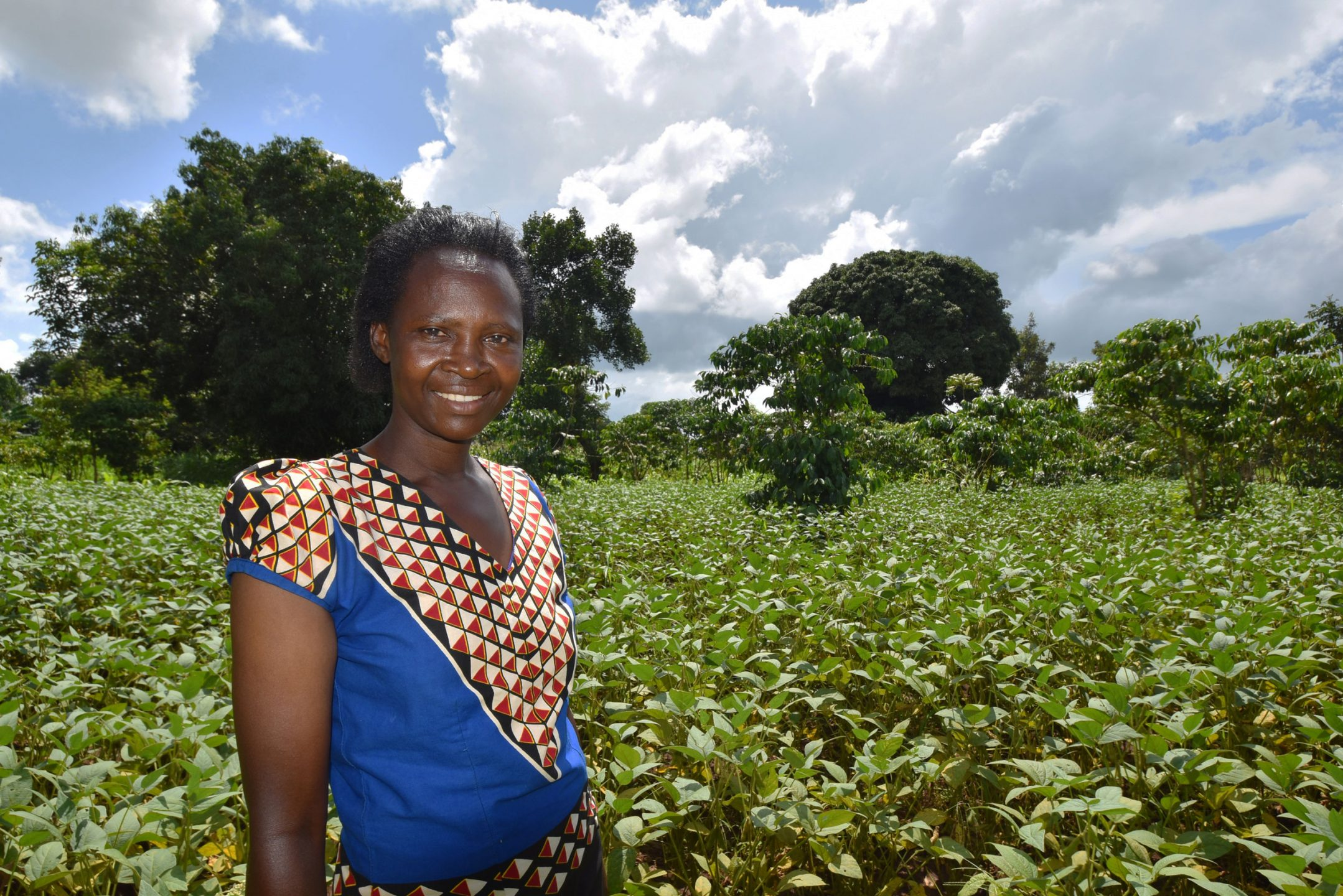 A woman stands in a field and smiles for a photo.