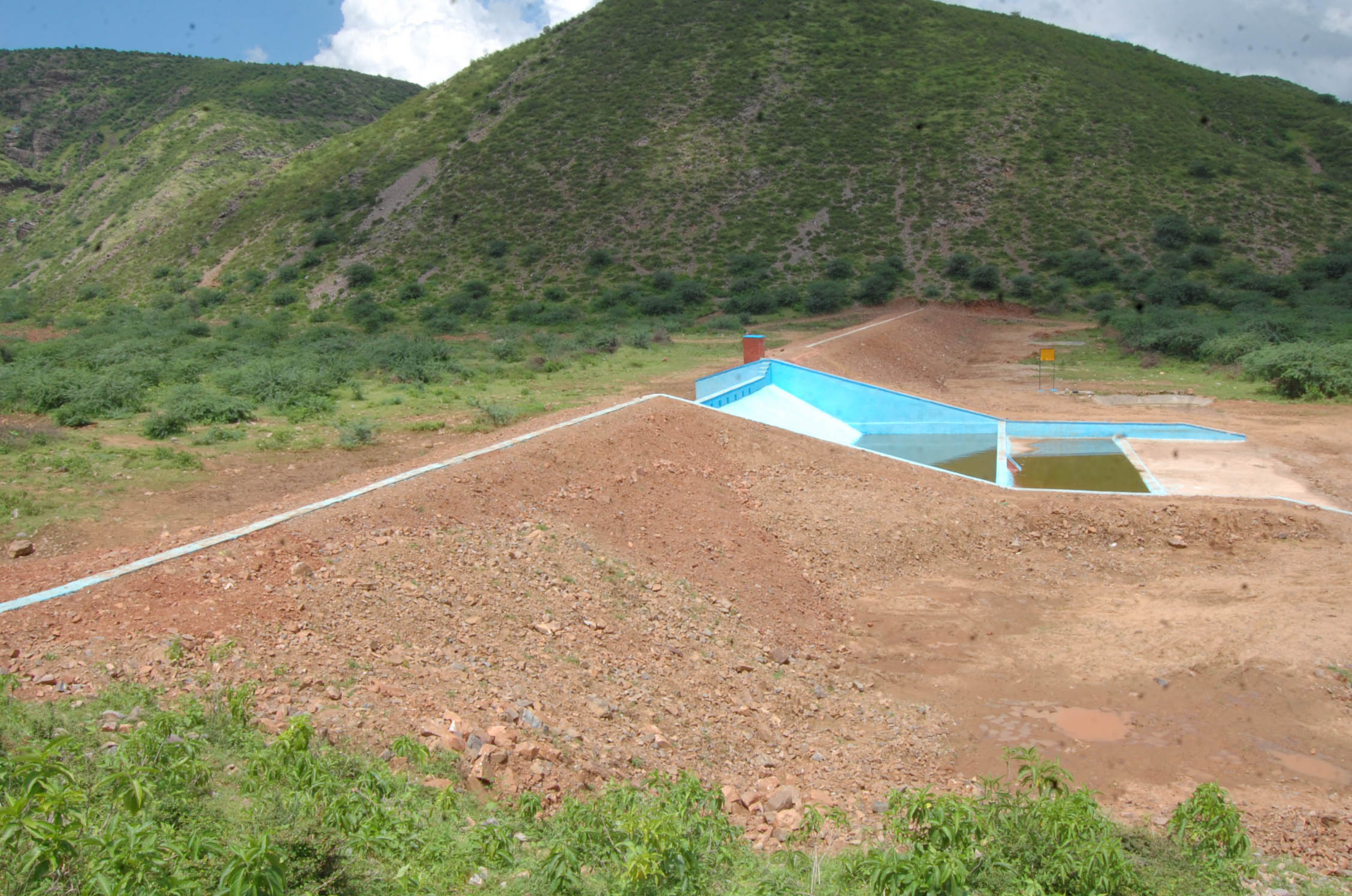 A check dam sits nestled in the hills.