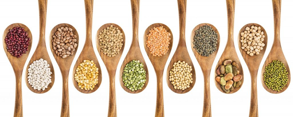 Wooden spoons containing pulses.