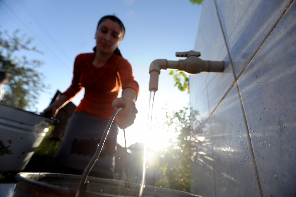 A woman fills a bucket with water.